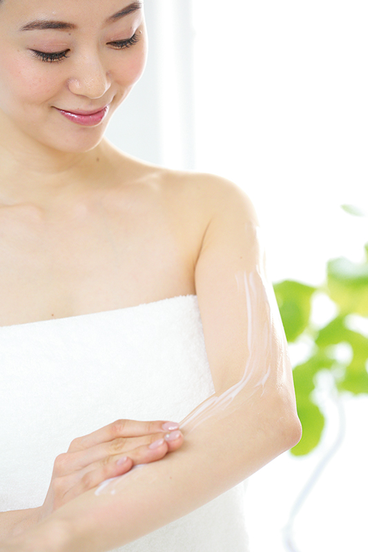 入浴後すぐにクリームを塗って保湿をする女性
