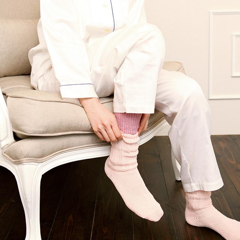 レッグウオーマーの上に靴下を履いているパジャマ姿の女性