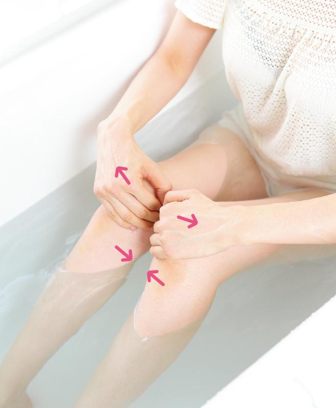 湯船に使った女性がひざを手で開こうとしている