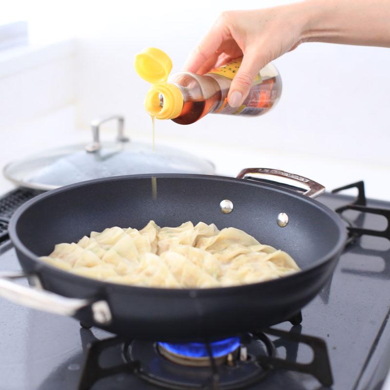 ヘルシー納豆餃子にごま油をかけている