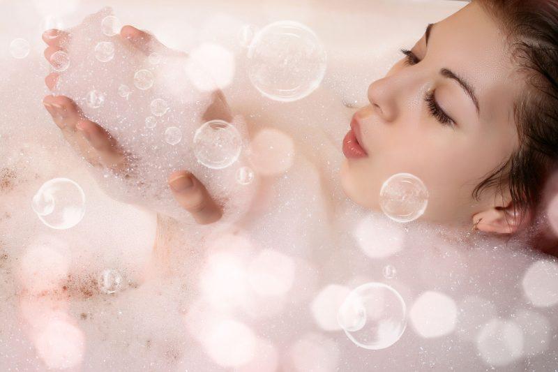 泡風呂に入っている女性が泡を手に取って吹き飛ばしている