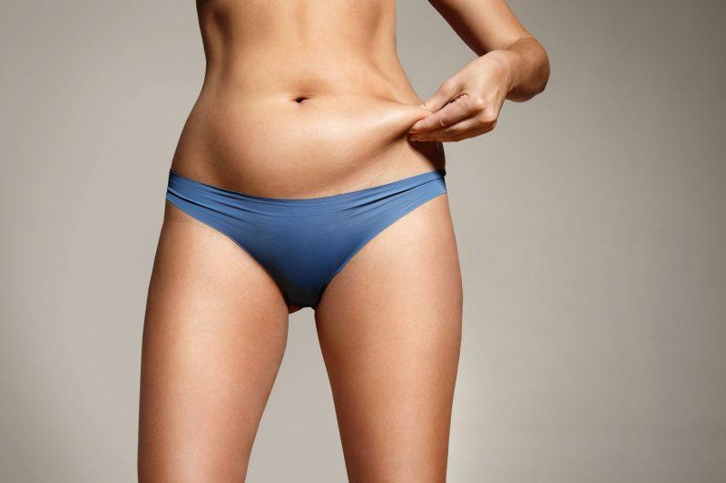 下着姿のスリムな女性がお腹にたまった脂肪をつまんでいる