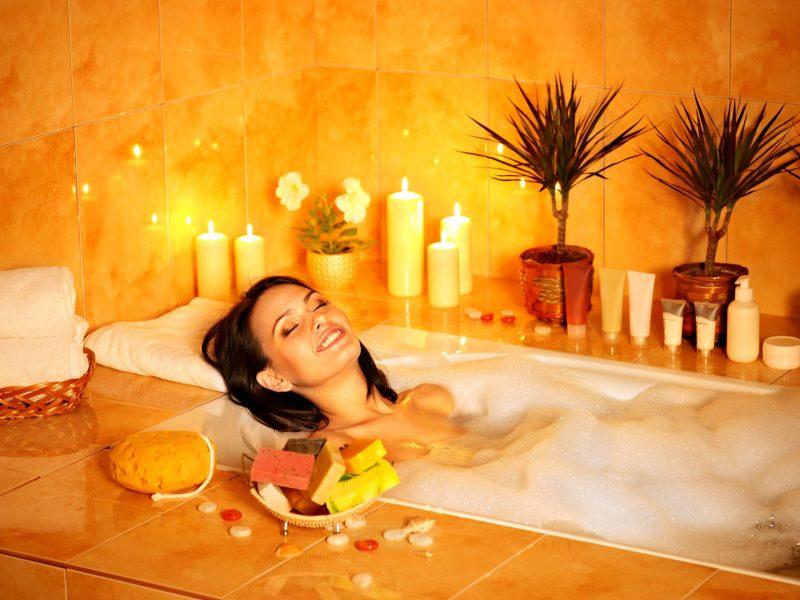 周囲にキャンドルなど癒しアイテムがおかれた浴室のバスタブでリラックスする女性
