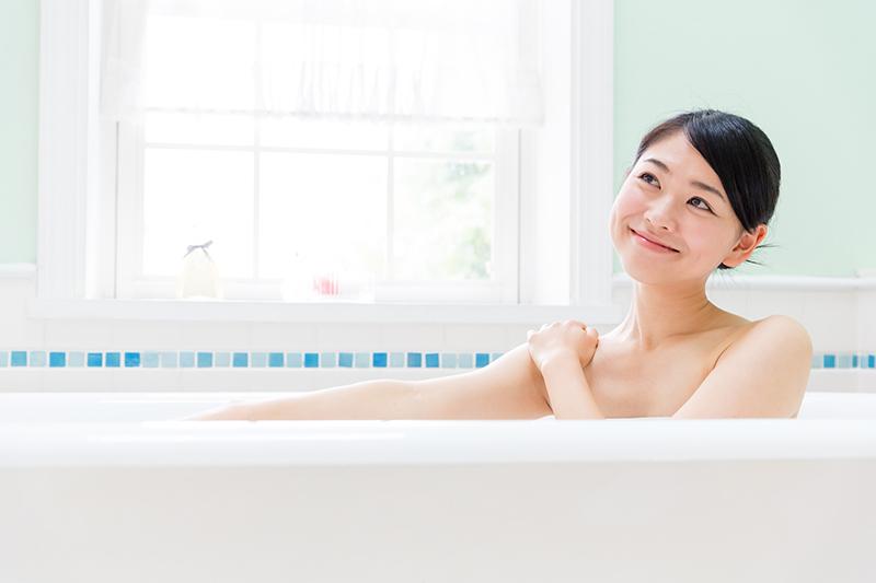 家庭の風呂につかってリラックスする女性