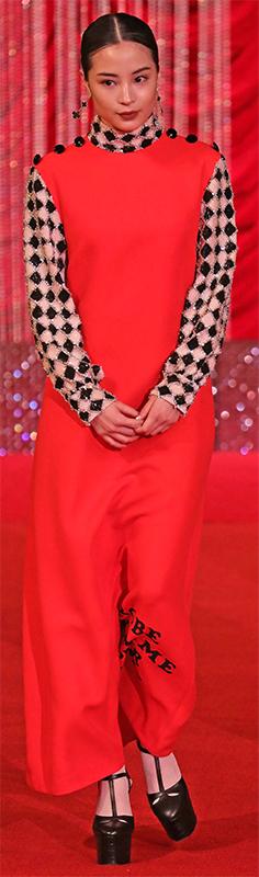 オレンジ色のジャンパースカートにモノクロのダイヤ柄のブラウスを着た広瀬すず