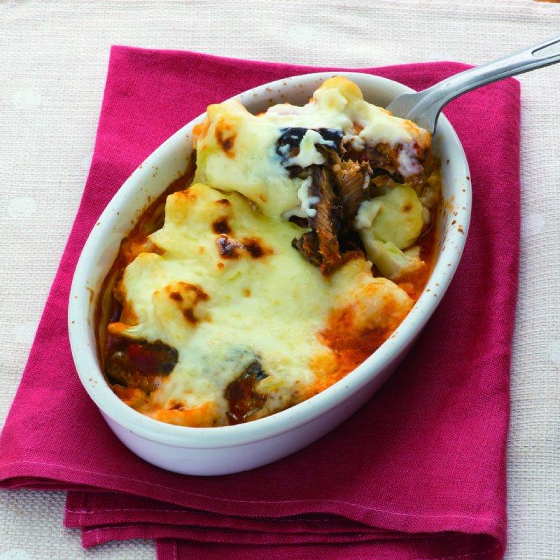 チーズがたっぷりかかったグラタンが白いオーバル皿に入っていて、フォークで一口分持ち上げている