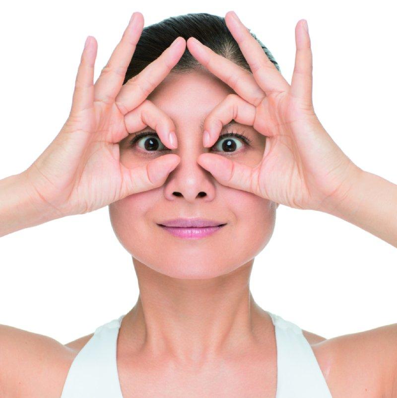 親指と人差し指で輪っかを作り、めがねのように目に当てる。人差し指は眉が動かないように固定する。目を閉じてから目をグッと開く。