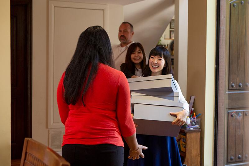 近藤が大きな収納ボックスを手に米国人の家を訪問している