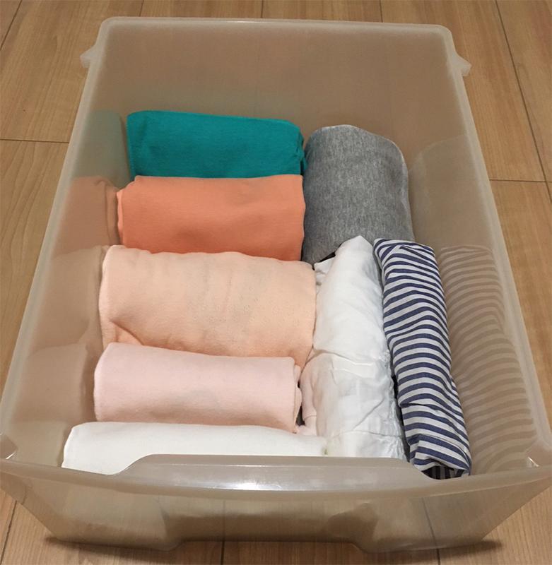 半透明の収納ケースに洋服を丸めて収納している