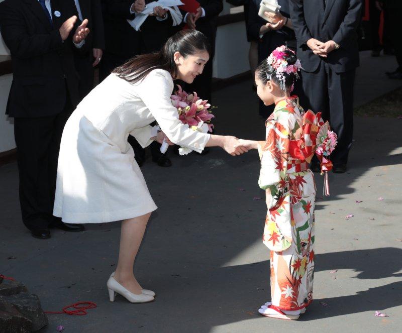 現地の着物を着た小さな女の子と握手を交わされる眞子さま