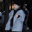 カイリー・ジェンナーがグレーのハーフコートに大ぶりな黒のタートルネックセーターで街角を歩いている