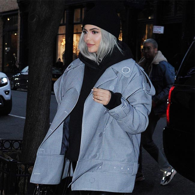 解離―ジェンナーがグレーのハーフコートに大ぶりな黒のタートルネックセーターで街角を歩いている