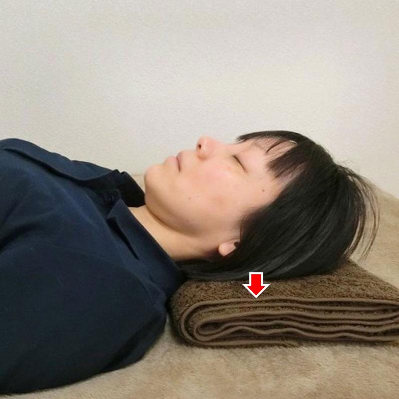 仰向けの状態で、後頭部で枕を押している