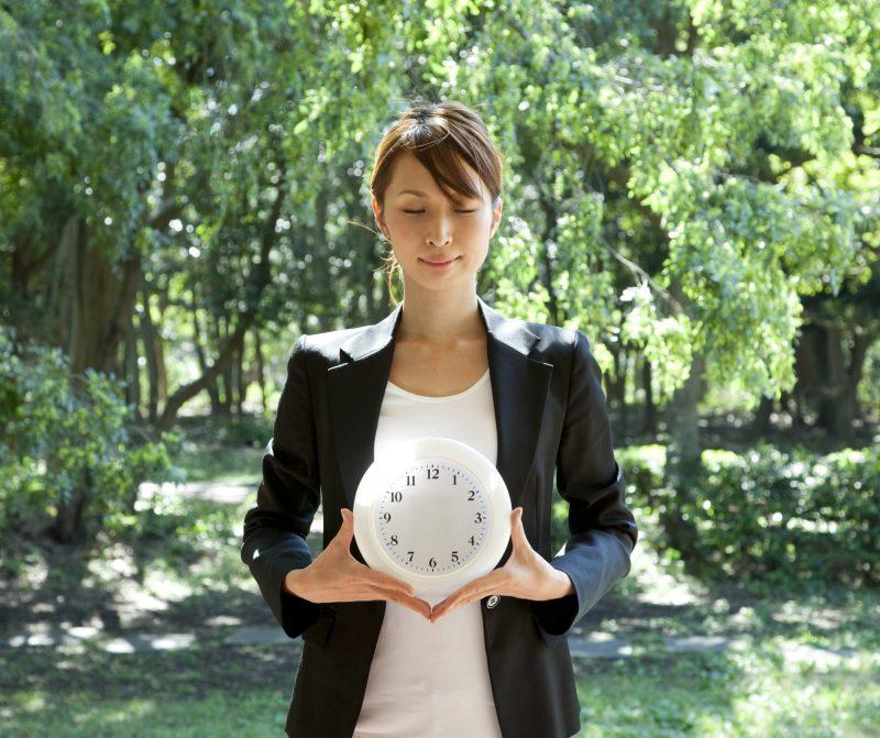 森の中で女性が針のない時計を持っている