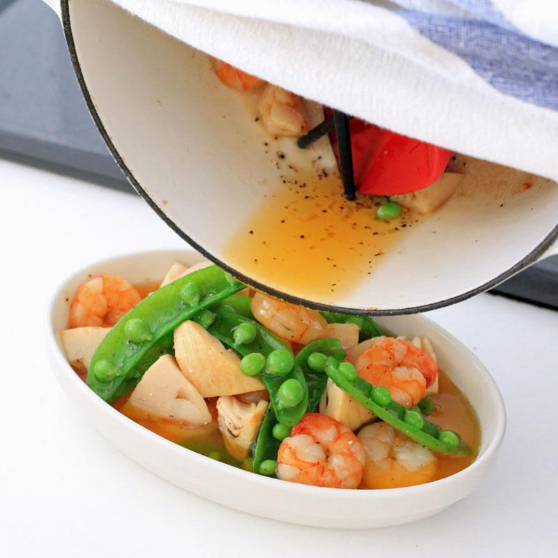 鍋から皿に盛り付けている「たけのこのアヒージョ」