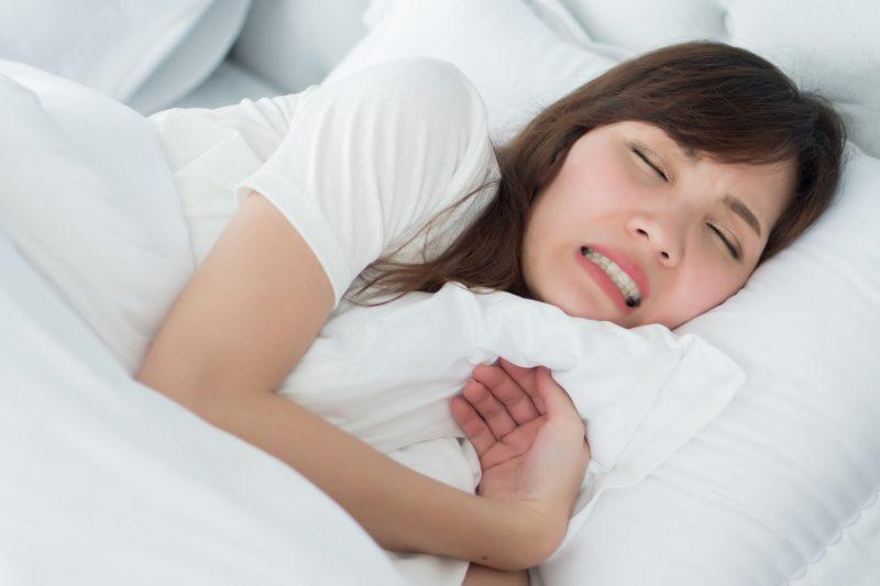 布団に寝て歯ぎしりをする女性