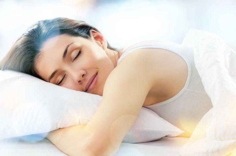 ベッドで夢を見ている女性のイメージ写真