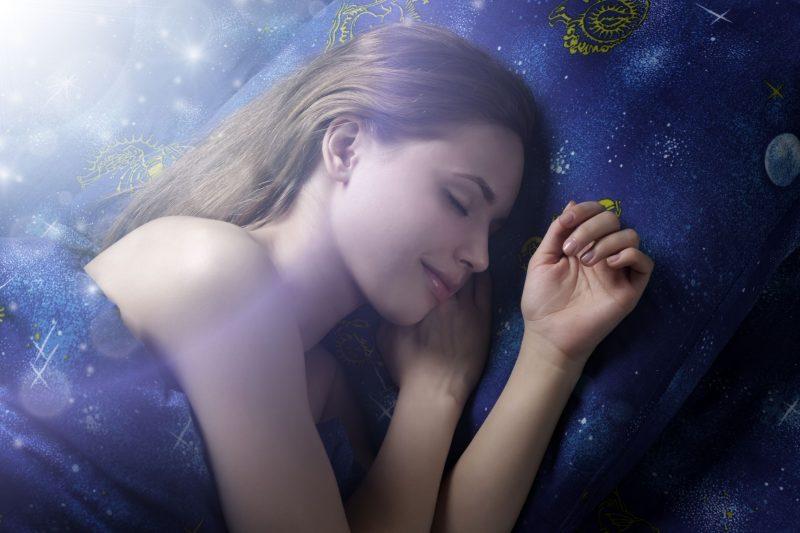 ベッドに入って夢を見ている女性のイメージ写真