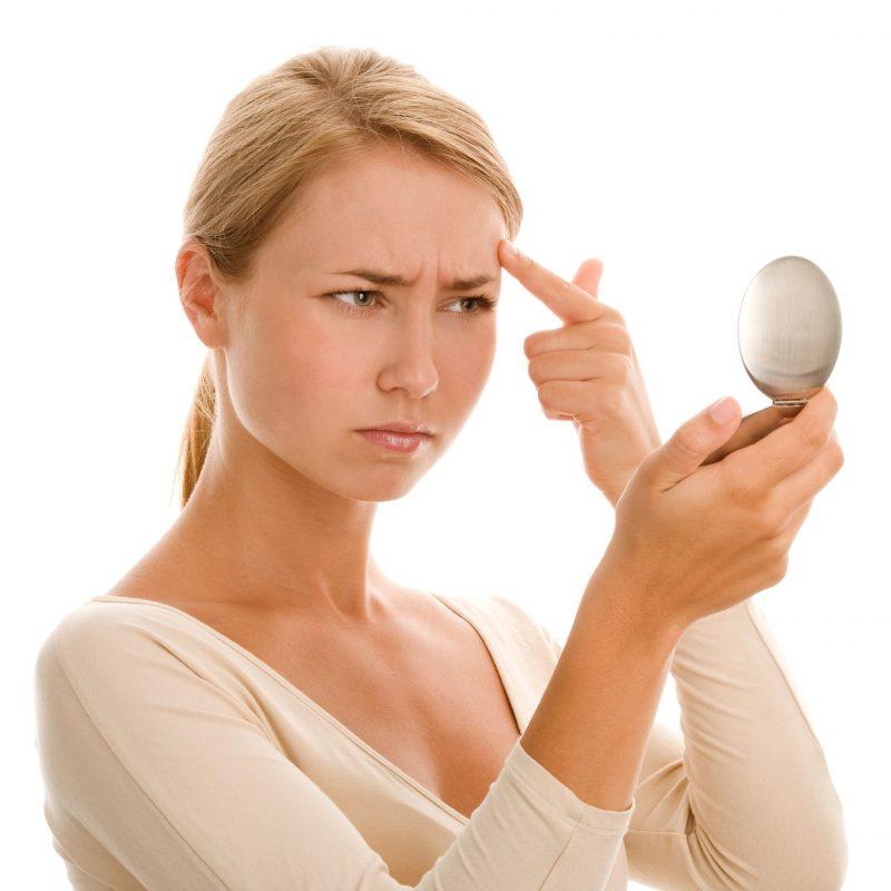 鏡を手に眉間のしわを気にする女性