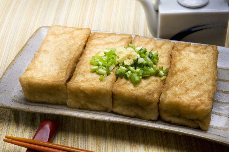 厚揚げをトースターで焼いて、万能ねぎとすりおろし生姜をのせたものが皿に盛りつけられている