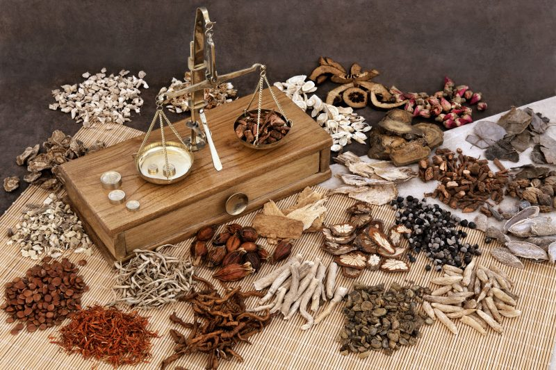 漢方薬の調合台と天秤、そのまわりに原料が並んでいる