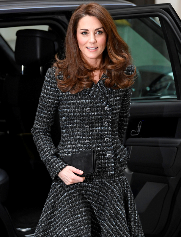 キャサリン妃が黒地に白の上品なチェックが入ったウールスーツに黒のクラッチバッグを持っている