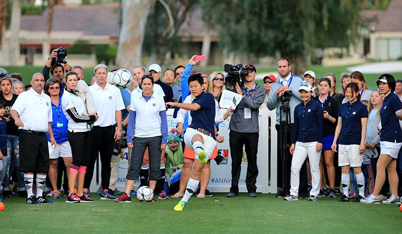 海堀あゆみさんがたくさんのギャラリーを背に、サッカーボールをキックしている。