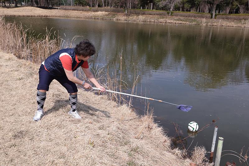 オバ記者が長い柄のついた網でボールを拾っている