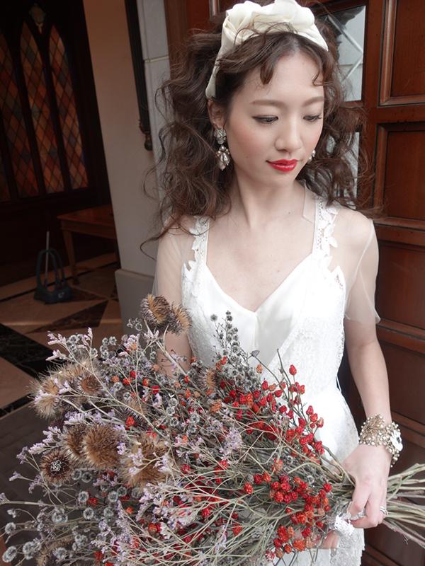 花束上のブーケを手にデザイン性の高いウエディングドレスを着た新婦