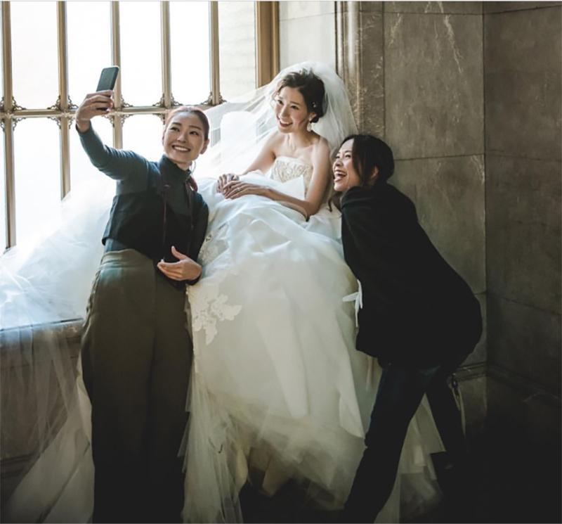 笑顔で新婦とスタッフと3人で記念撮影する服部さん