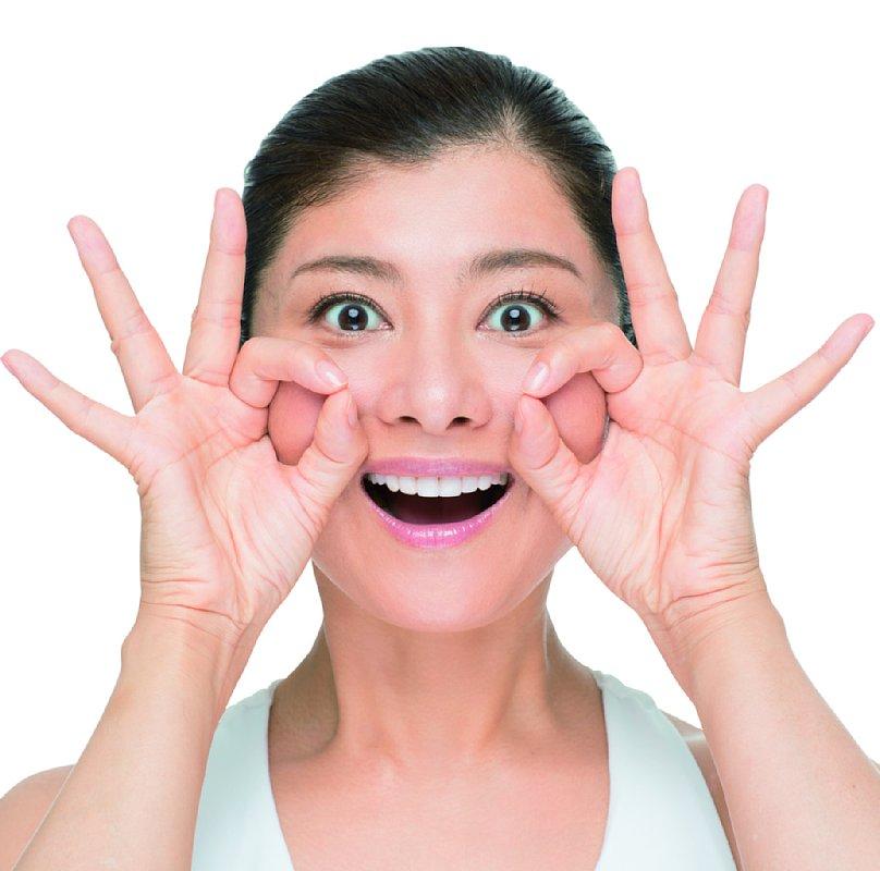 上の歯だけを見せて、にっこり笑い、親指と人差し指で頬におだんごを作る顔ヨガのポーズ
