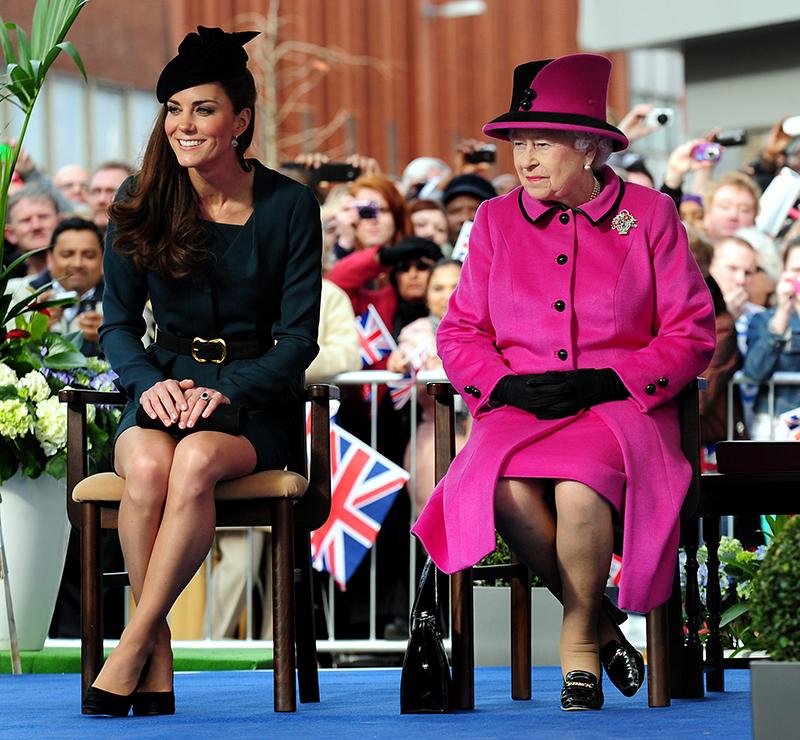 正装をしたエリザベス女王とキャサリン妃が椅子に座り、足首をクロスさせている