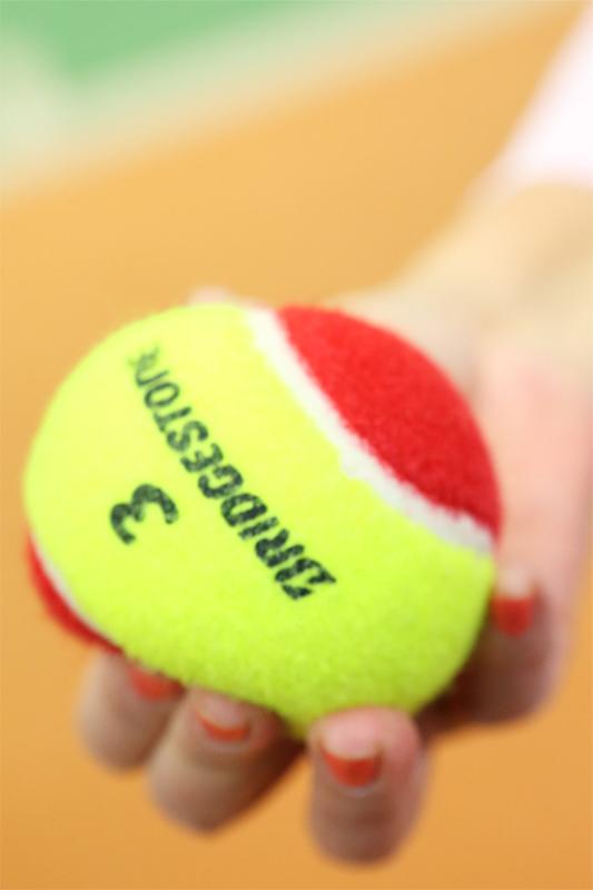 やわらかいジュニア用のテニスボールを手で軽くつぶしている
