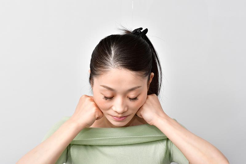 両拳をあごの中心に当て、指の谷間であごから耳の下までをさすり上げる