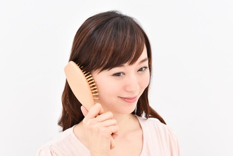 耳にブラシを置き、右回し左回しをしながらやさしく指圧している女性