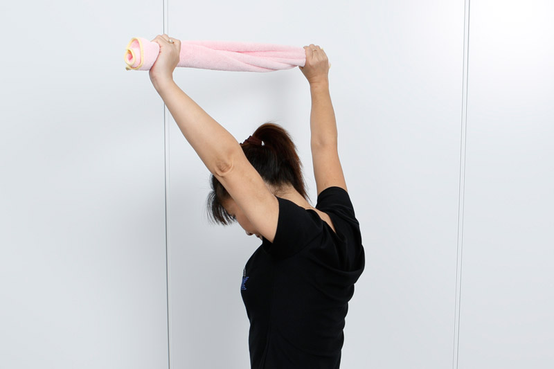 両手でタオルを持ち、頭の上に掲げる女性