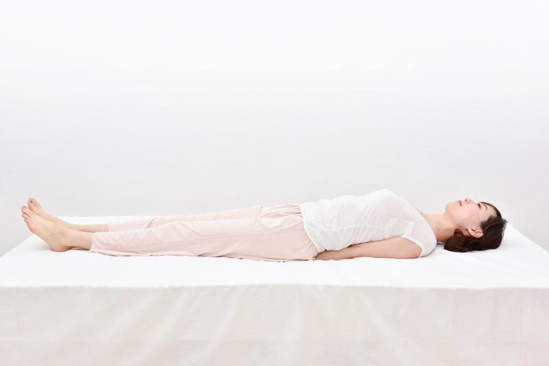 ベッドの上で仰向けになり、手の平を下に向け腕全体を背中やお尻の下に入れる