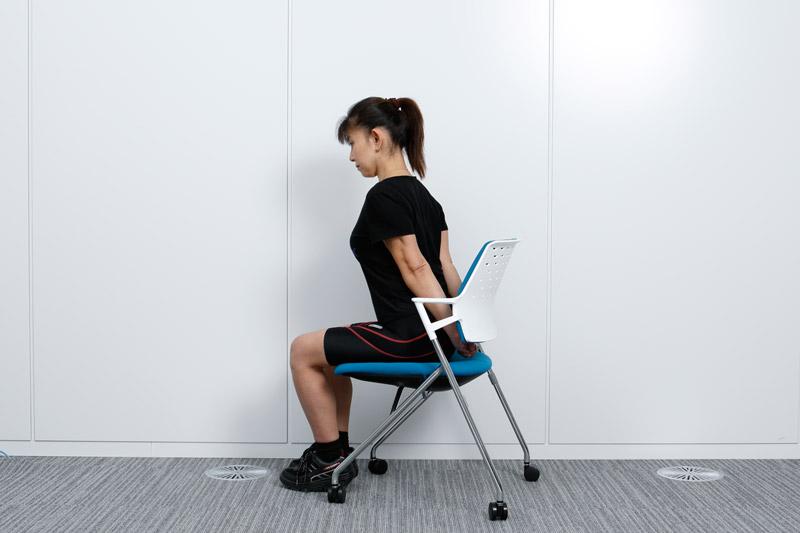 椅子に座った状態で、手を後ろで組む