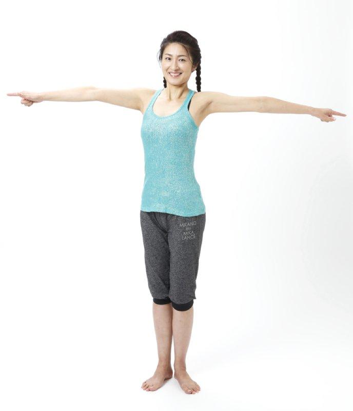 腕を肩まで上げて大きく広げ、下半身、肩は極力動かさずにツイストする女性