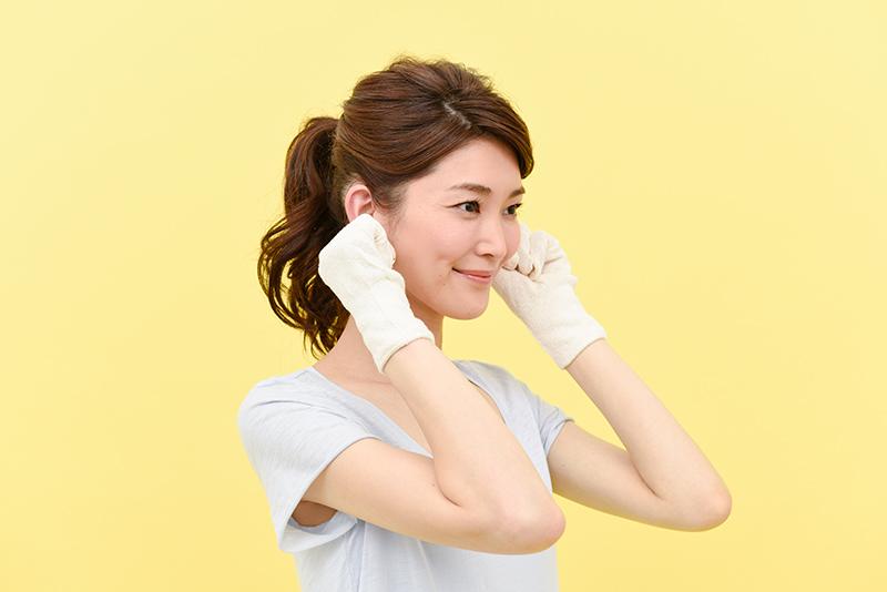 人差し指と親指で耳を挟んで指の腹でやさしく、耳全体をもみほぐしている女性