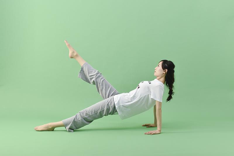 左足をしっかりと床につけ、右脚を持ち上げる女性