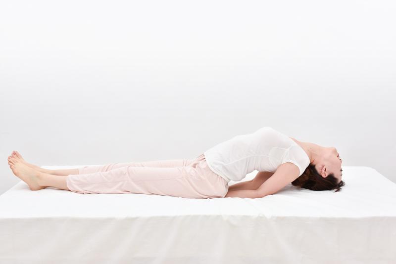 頭を後ろに反らし、頭のてっぺんをゆっくり床について喉を伸ばす。