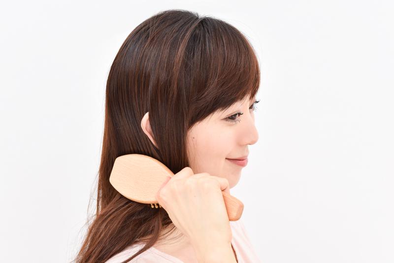 頭頂部から首までブラシでランダムに頭皮をゆっくりと刺激している女性