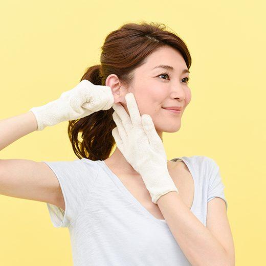 右耳を引っ張り上げながら、左手で左耳下をおさえている女性