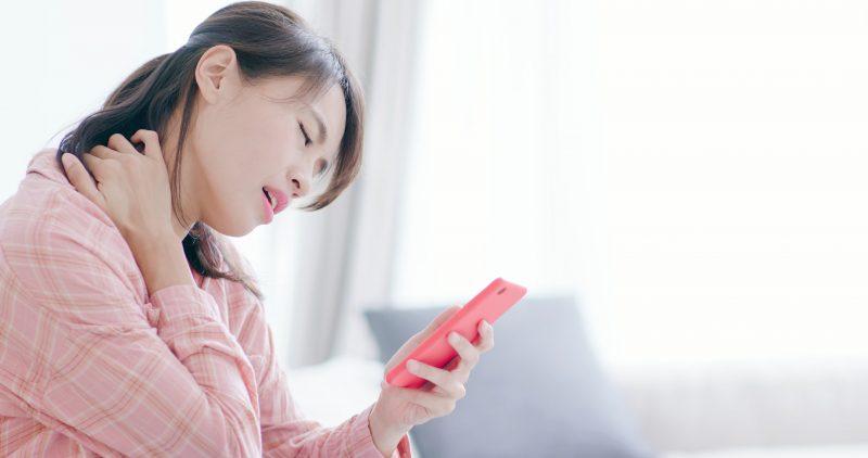 スマートフォンを手に首を押さえて苦しそうな女性