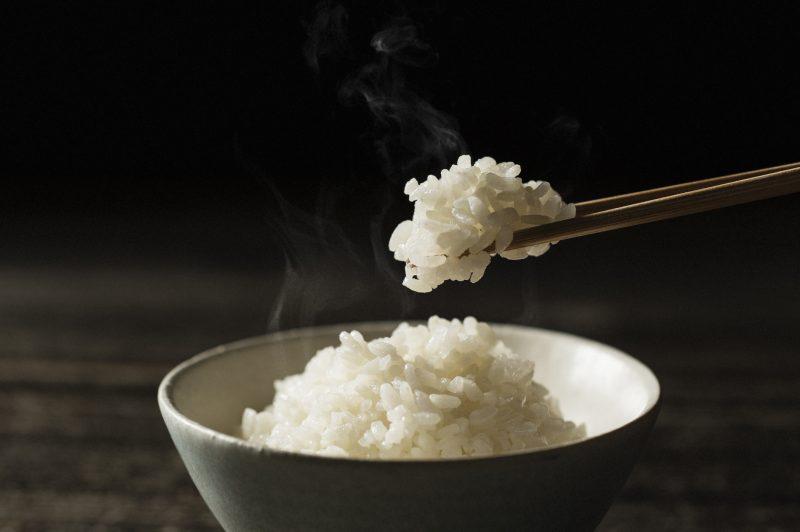 白米が茶碗いっぱいに入って、お箸で一口分すくいあげている