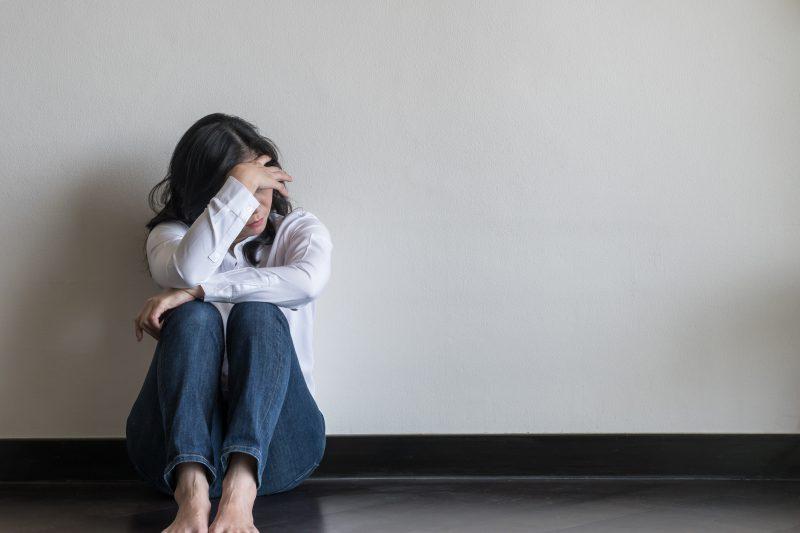 更年期障害によるうつ症状で部屋で頭を抱える女性