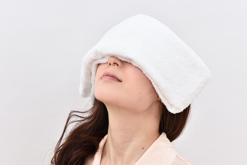 ハンドタオルを顔にのっけている女性