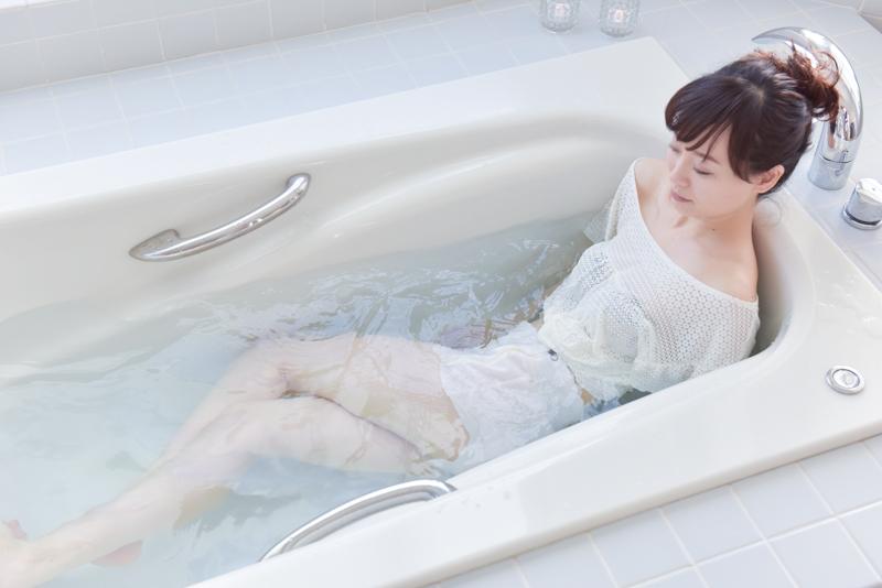 手で浴槽を押しながらお尻を浮かし、右側に体をひねる女性