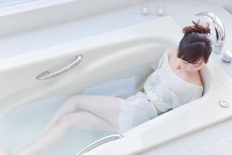 お風呂で体をねじった方とは逆方向に顔を向け、顔を向けた側の肘を曲げる女性